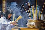 Woman with incense inside a temple, Ho Chi Minh City (Saigon), Vietnam, Indochina, Asia