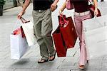 Couple marchant avec sacs à provisions sur Königsallee, Düsseldorf, Nord Westphalie, Allemagne, Europe