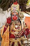 A supposed Holy man dressed as Hanuman, the Hindu monkey god, posing for photographs, Durbar Square, Kathmandu, Nepal, Asia