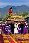 Portent un énorme flotteur en bois du Christ sur tapis de sciure colorée au cours de la procession de Pâques à Antigua, au Guatemala, l'Amérique centrale