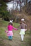 Zwei Mädchen gehen mit Ostern Körbe