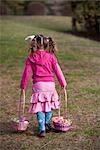 Junge Mädchen gehen mit Ostern Körbe