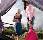 Girls putting sleeping bags in tent