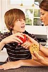 Mère essayant d'obtenir des fils de manger une pomme au lieu d'un Cookie