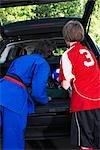 Garçons en karaté et uniformes de Soccer la voiture de livraison