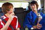 Garçons en karaté et uniformes de Soccer dans la banquette arrière de voiture