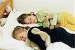 Sisters sleeping in bed, cuddling stuffed animals