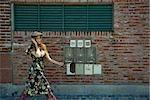 Jeune femme en vêtements branchés marchant sur le trottoir, chat sur téléphone portable