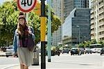 Trendy young woman walking along city street