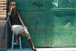 Mode jeune femme assise sur le tabouret en face des murs graffités