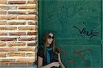 Jeune femme à lunettes de soleil appuyé contre le mur