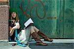 Junge Frau sitzt auf dem Boden mit Buch und Getränk, Wegsehen