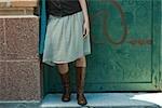 Jeune femme de penchement de vêtements branchés contre le mur, partie basse