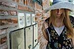Jeune femme portant grand chapeau, regardant vers le bas