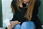 Jeune femme se penchant sur le coude, tenant de la coupe, recadrée vue