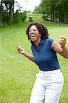 Frau lachend auf Golfplatz