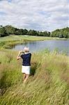 Vue arrière du femme jouer au golf dans les hautes herbes