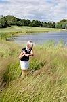 Vue latérale d'une femme, jouer au golf dans les hautes herbes