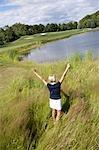 Rückansicht des Frau-Golfen in hohem Gras