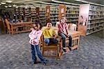 Portrait of three school friends in library