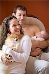 Portrait de couple jeune heureux holding bébé ans 3 mois et le chien à la maison