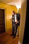 Senior African American jazz musician standing in hallway with trumpet