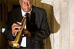Senior African American musician holding trumpet near door