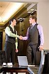 Portrait of multi-ethnic businessmen shaking hands in modern lobby