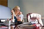 Portrait de jeune femme assise au bébé de tenue de bureau et sur le téléphone