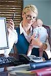 Portrait de bébé holding jeune femme d'affaires dans les bras au travail