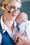 Portrait de bébé holding jeune femme d'affaires et sur le téléphone