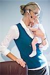 Portrait de bébé holding jeune femme d'affaires et sur le téléphone au travail