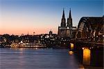 Bateau sur le Rhin décoré pour Noël, la cathédrale de Cologne et pont Hohenzollern au crépuscule, Cologne, Nord-Rhénanie-Westphalie, Allemagne