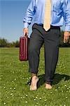 Businessman Walking Barefoot on Grass