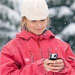 Gros plan d'une femme à l'aide de PDA à l'extérieur en hiver, Whistler, Colombie-Britannique, Canada