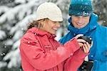 Gros plan d'un Couple à l'aide de PDA à l'extérieur en hiver, Whistler, Colombie-Britannique, Canada
