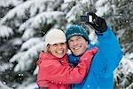 Couple en prenant l'auto-portrait avec le téléphone appareil photo à l'extérieur en hiver, Whistler, Colombie-Britannique, Canada