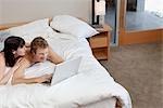 Couple au lit à l'aide d'ordinateur portable
