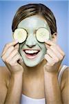 Femme de boue masque et concombre de tranches souriant