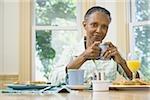Portrait d'une femme senior tenant une tasse de café à la table du petit déjeuner