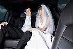 Gros plan d'un couple de jeunes mariés, assis dans une voiture et en regardant de l'autre