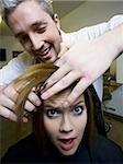 Woman having hair cut by hairdresser