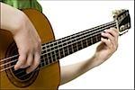 Fille avec bretelles jouant guitare souriant