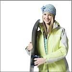 Fille avec le chapeau d'hiver et les skis souriant