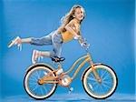 Fille sur bicyclette orange à genoux sur le siège avec le pied jusqu'à