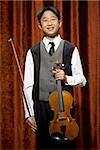 Garçon avec violon et archet souriant