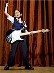 Garçon sur scène en jouant la guitare électrique