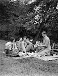 ANNÉES 1920 ANNÉES 1930 4 PERSONNES 2 COUPLES HOMMES FEMMES ASSIS SUR LE SOL AYANT UNE NOURRITURE PIQUE-NIQUE ÉTÉ