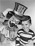 1950s CLOWN WITH TOP HAT ARM AROUND BOY IN STRIPED SHIRT