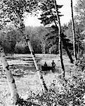 1940s PAIR OF MEN CANOEING IN LAKE OF THE WOODS ONTARIO CANADA
